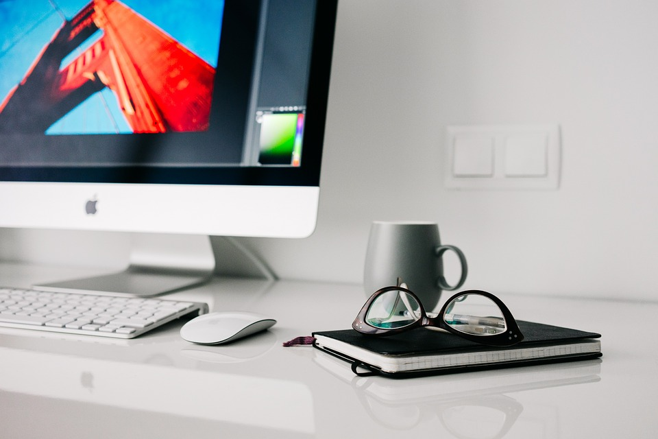White Desktop With Display, Keyboard, Coffee Cup, Glasses